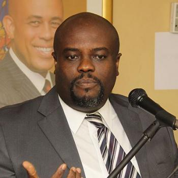 rudy_heriveaux__ministre_de_la_communication with Martelly portrait behind him.jpg